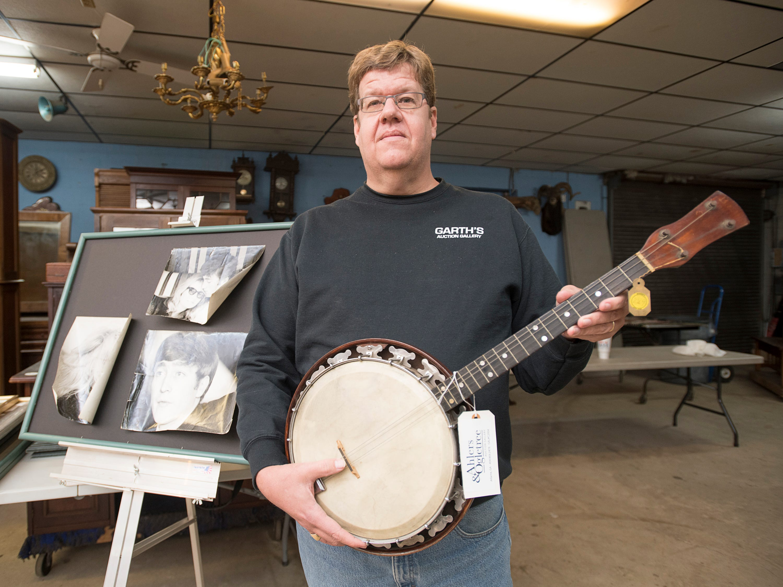 Owner Robert Garth holds a George Harrison banjo at Garth's Auction & Antiques on Navy Boulevard in Pensacola on Wednesday, November 28, 2018.  The banjo and other items will be up for sale during their auction on Friday, November 30th.