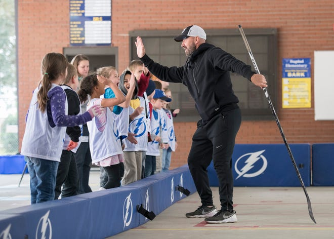 Former NHL and Ice Pilots star Glen Metropolit, right, high fives students after scoring a goal during a hockey clinic at Bagdad Elementary School in Milton on Wednesday, November 28, 2018.