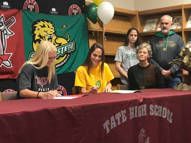 Tate soccer standouts Makenna Stafford (left at table) and Avery Royer (right at table) sign letters of intent to join Troy and Southeastern respectively on Nov. 28, 2018 at Tate High School.