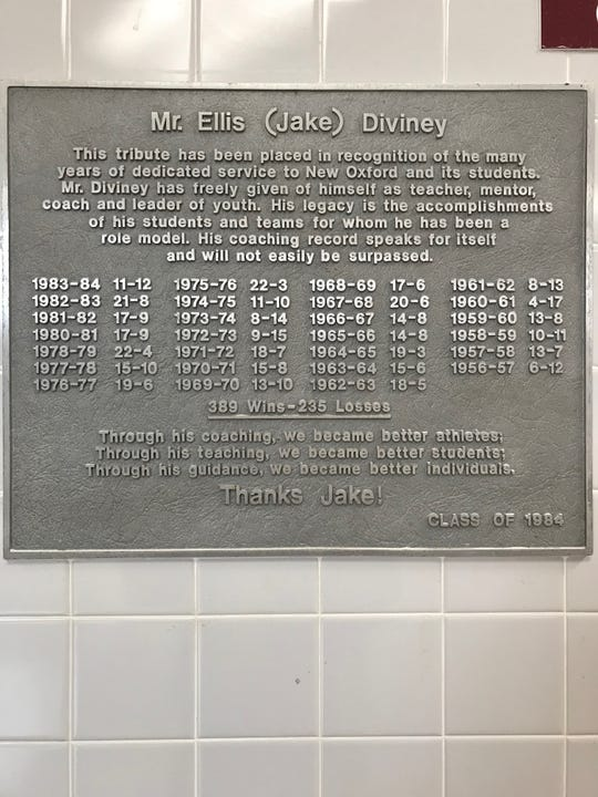 A plaque honoring Jake Diviney, the 30-year head coach of the New Oxford basketball team, is on display outside the school gym.