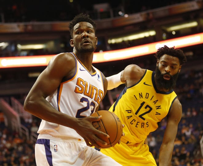 Suns center Deandre Ayton spins around Pacers guard Tyreke Evans during the first quarter of a game Nov. 27.