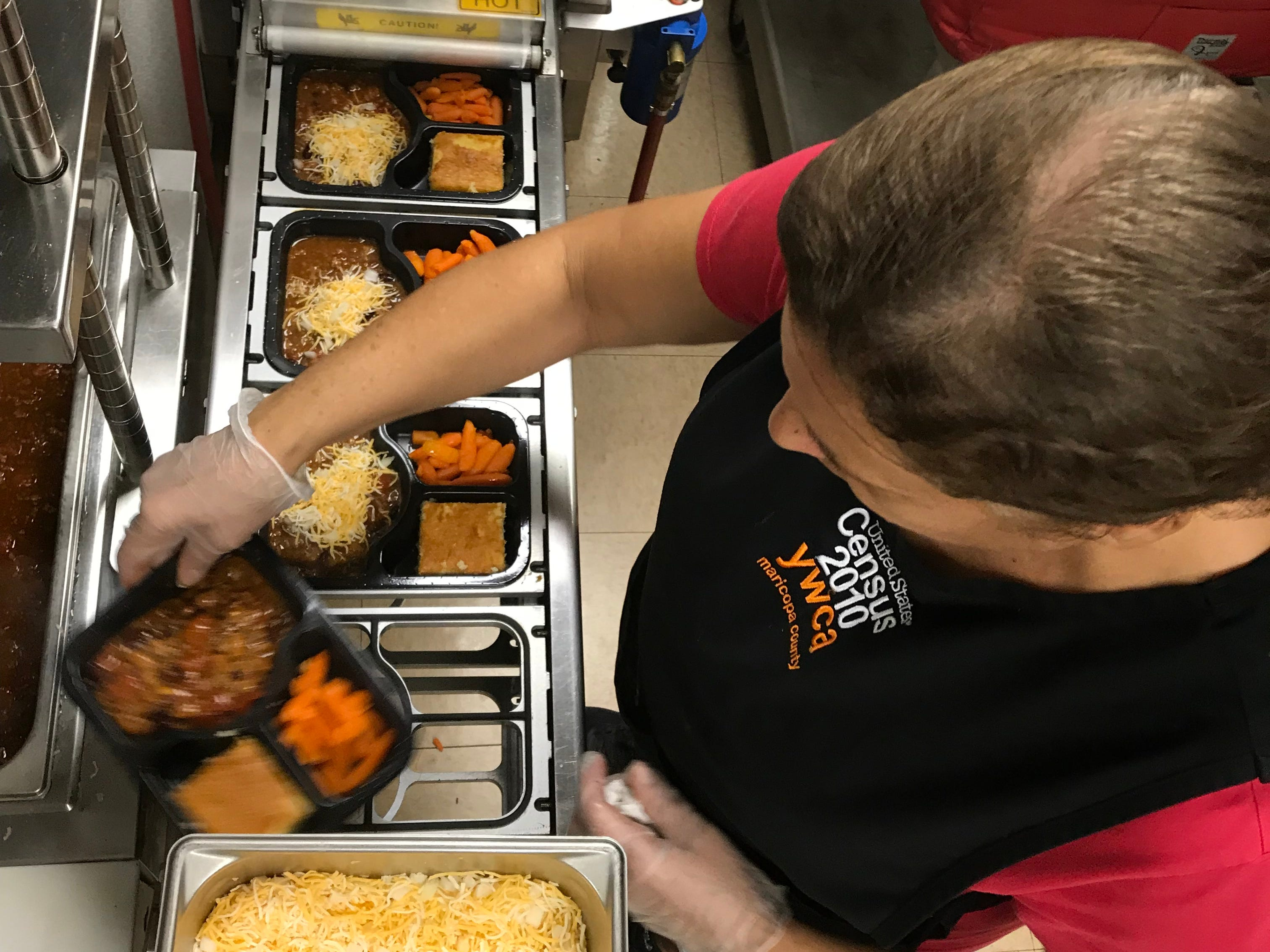 A worker assembles the hot meal and sends the trays through a machine that seals each tray in plastic wrap.