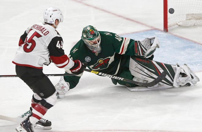 Arizona Coyotes' Josh Archibald, left, scores his second of two third-period goals off Minnesota Wild goalie Devan Dubnyk, right, during an NHL hockey game Tuesday, Nov. 27, 2018, in St. Paul, Minn. The Coyotes won 4-3.