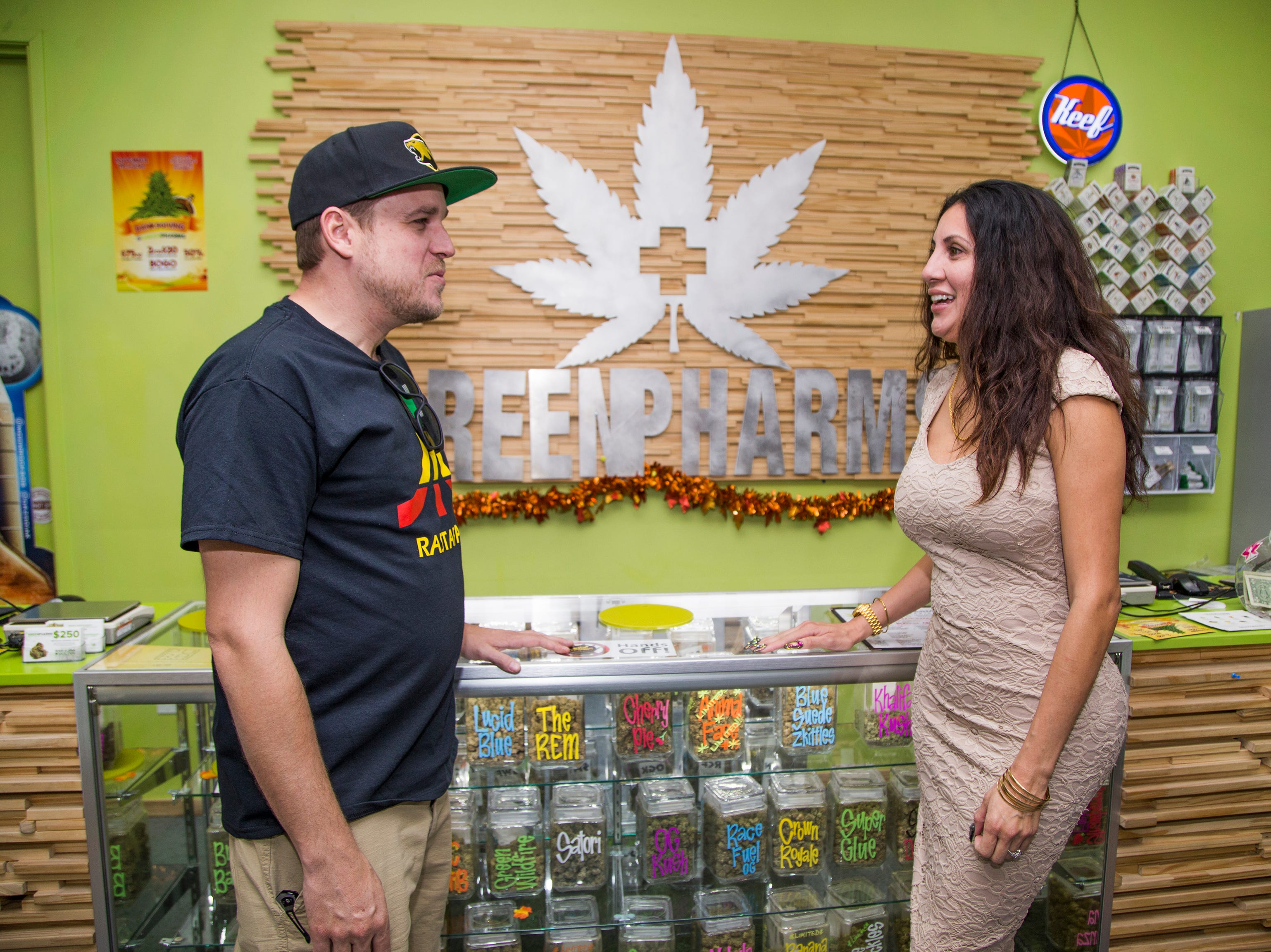 Marie Paredes Saloum, owner of GreenPharms Dispensary, speaks with customer Trevor Donaldson in the store in Mesa on Nov. 13, 2018.