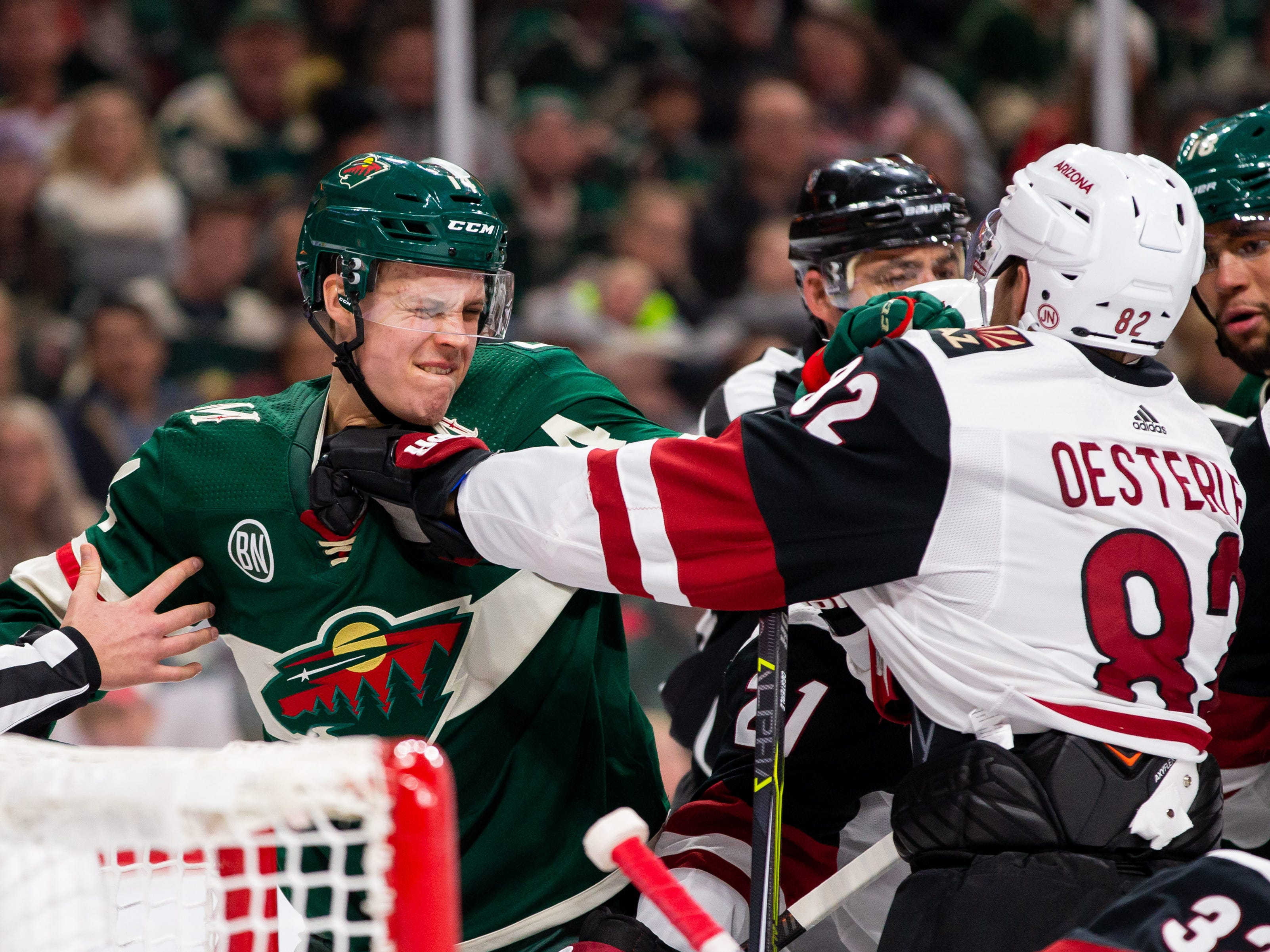 Nov 27, 2018; Saint Paul, MN, USA; Minnesota Wild forward Joel Eriksson Ek (14) and Phoenix Coyotes defenseman Jordan Oesterle (82) push after the whistle in the second period at Xcel Energy Center. Mandatory Credit: Brad Rempel-USA TODAY Sports
