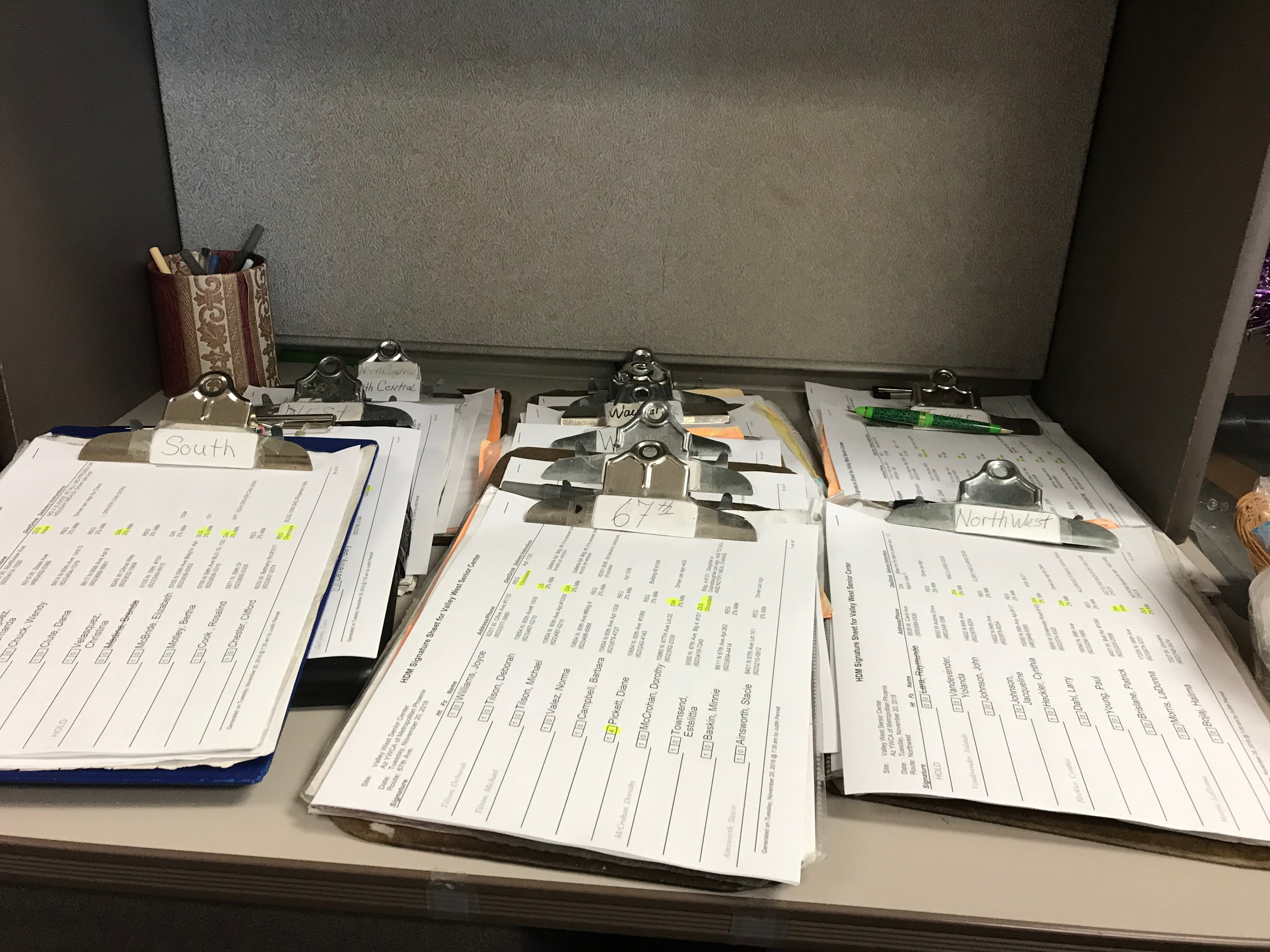 Clipboards containing the  checklists for that day's routes wait for drivers inside the Meals on Wheels office.