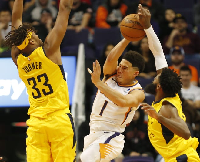 Phoenix Suns guard Devin Booker (1) loses the ball to Indiana Pacers guard Tyreke Evans (12) while defended by center Myles Turner (33) during the fourth quarter November 27.