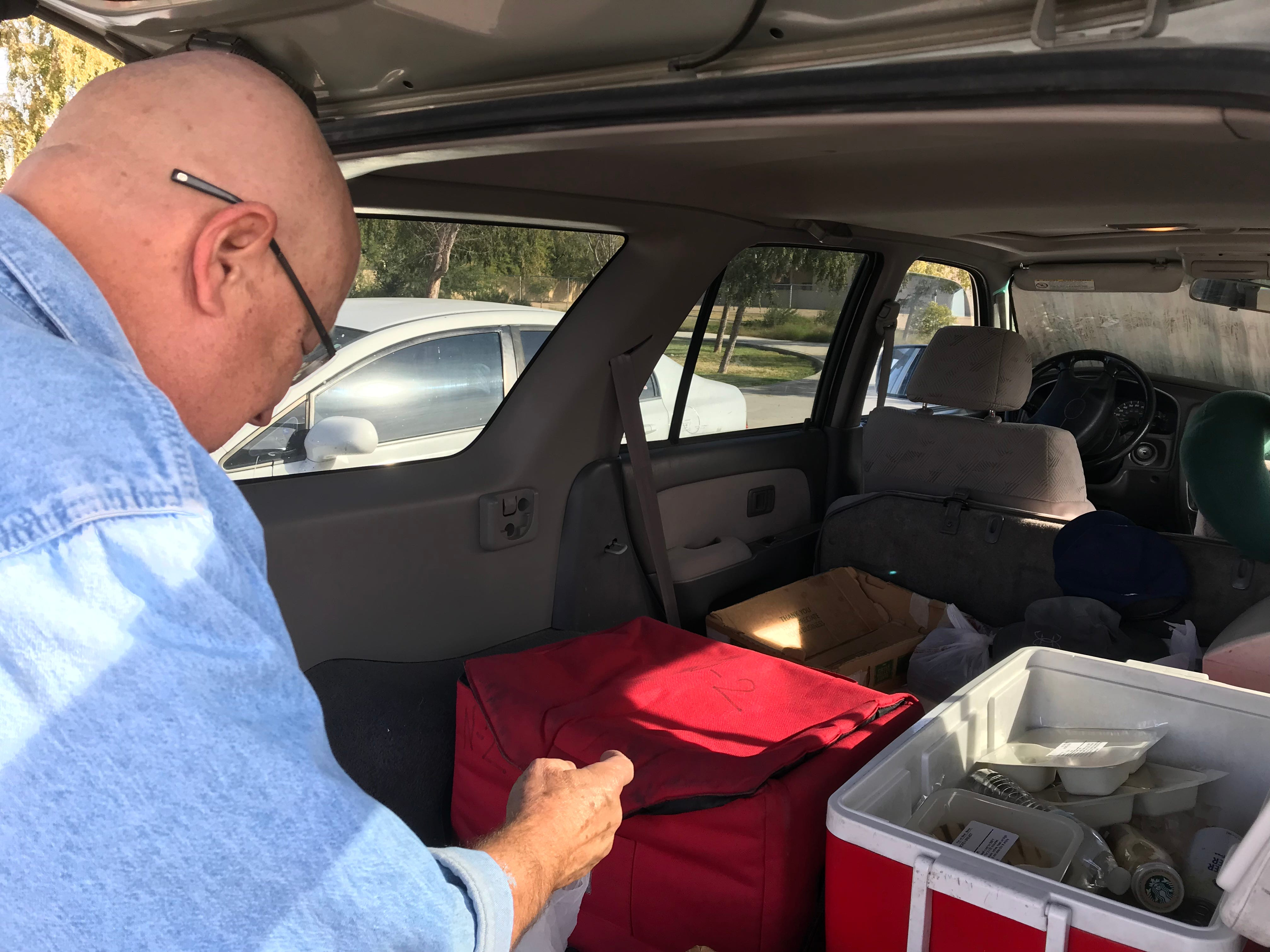 Meals on Wheels driver Dennis O'Melia double-checks his list before departing on his delivery run.
