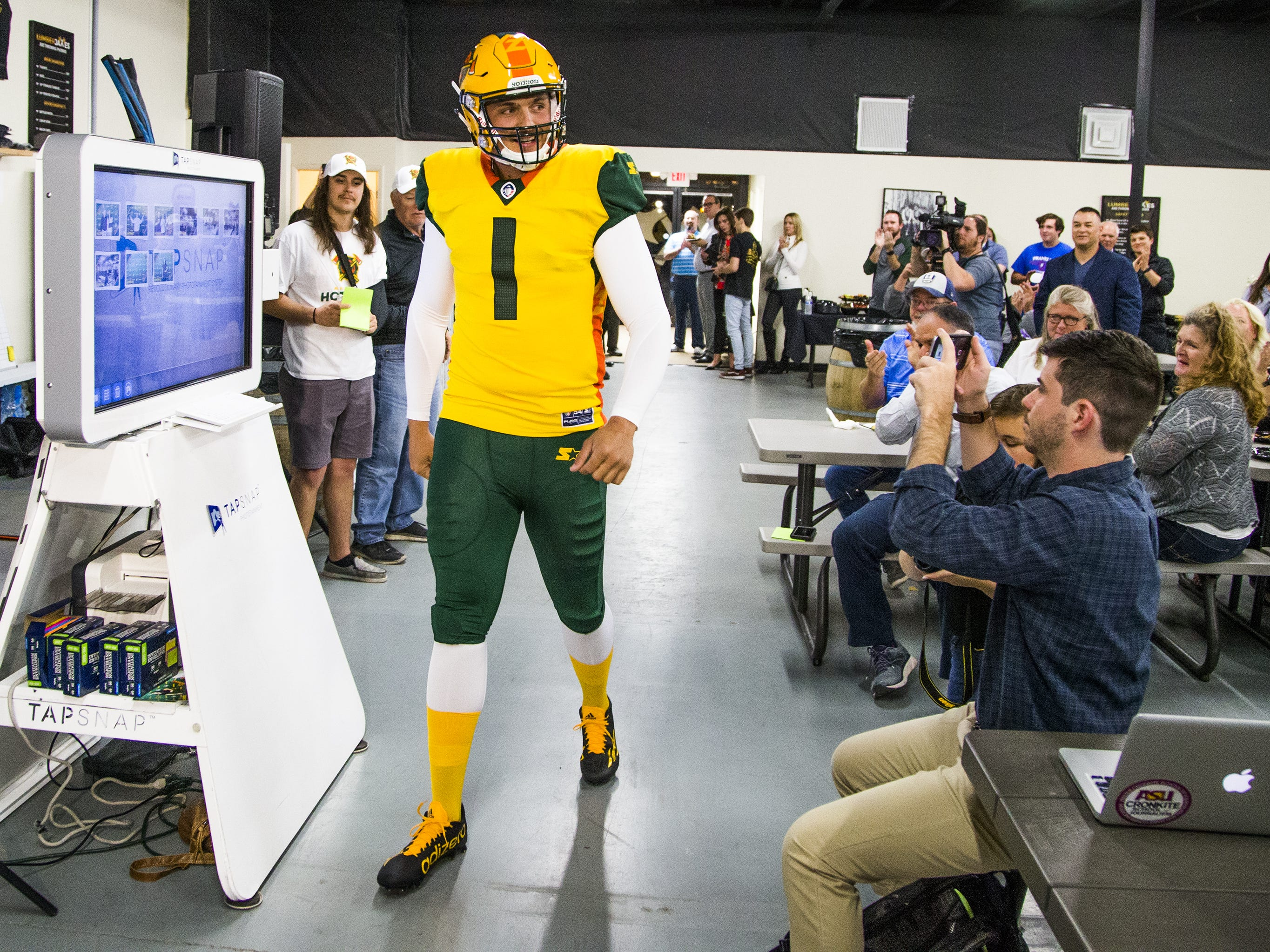 Nick Dooley, a longsnapper, unveils the new uniform for the Arizona Hotshots professional football team at an event at Lumberjaxes in Tempe, Tuesday, November 27, 2018.