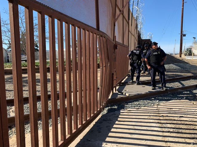 Dozens of customs officers guard a railroad crossing east of the San Ysidro crossing in San Diego, following Sunday's attempt by groups of migrants to rush the border.