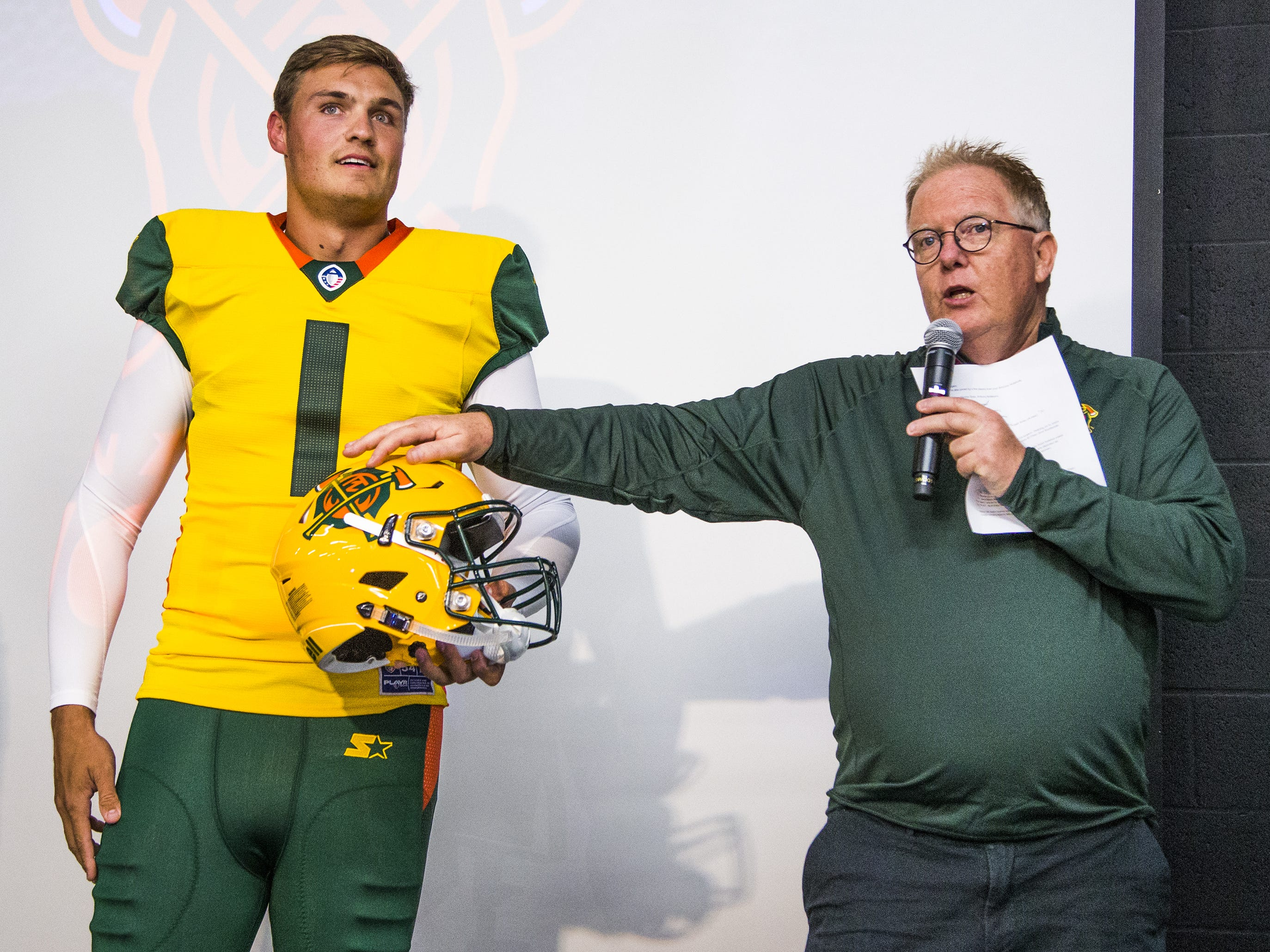 Nick Dooley, a longsnapper, wears the new uniform for the Arizona Hotshots professional football team as radio announcer Jeff Munn shows off the helmet decal at an event at Lumberjaxes in Tempe, Tuesday, November 27, 2018.