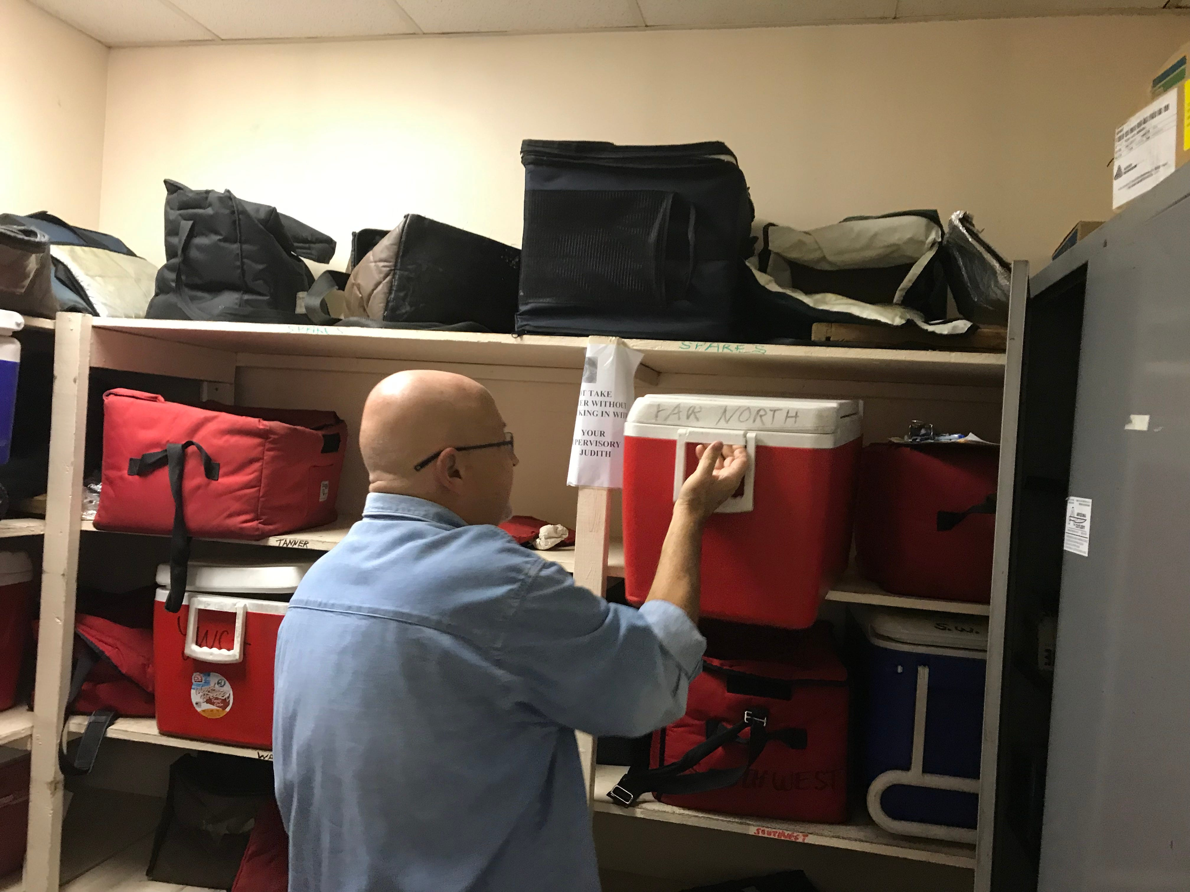 Dennis O'Melia, a 69-year-old retiree, grabs a cooler he'll need to store milk, juice and frozen meals along his Meals on Wheels route.