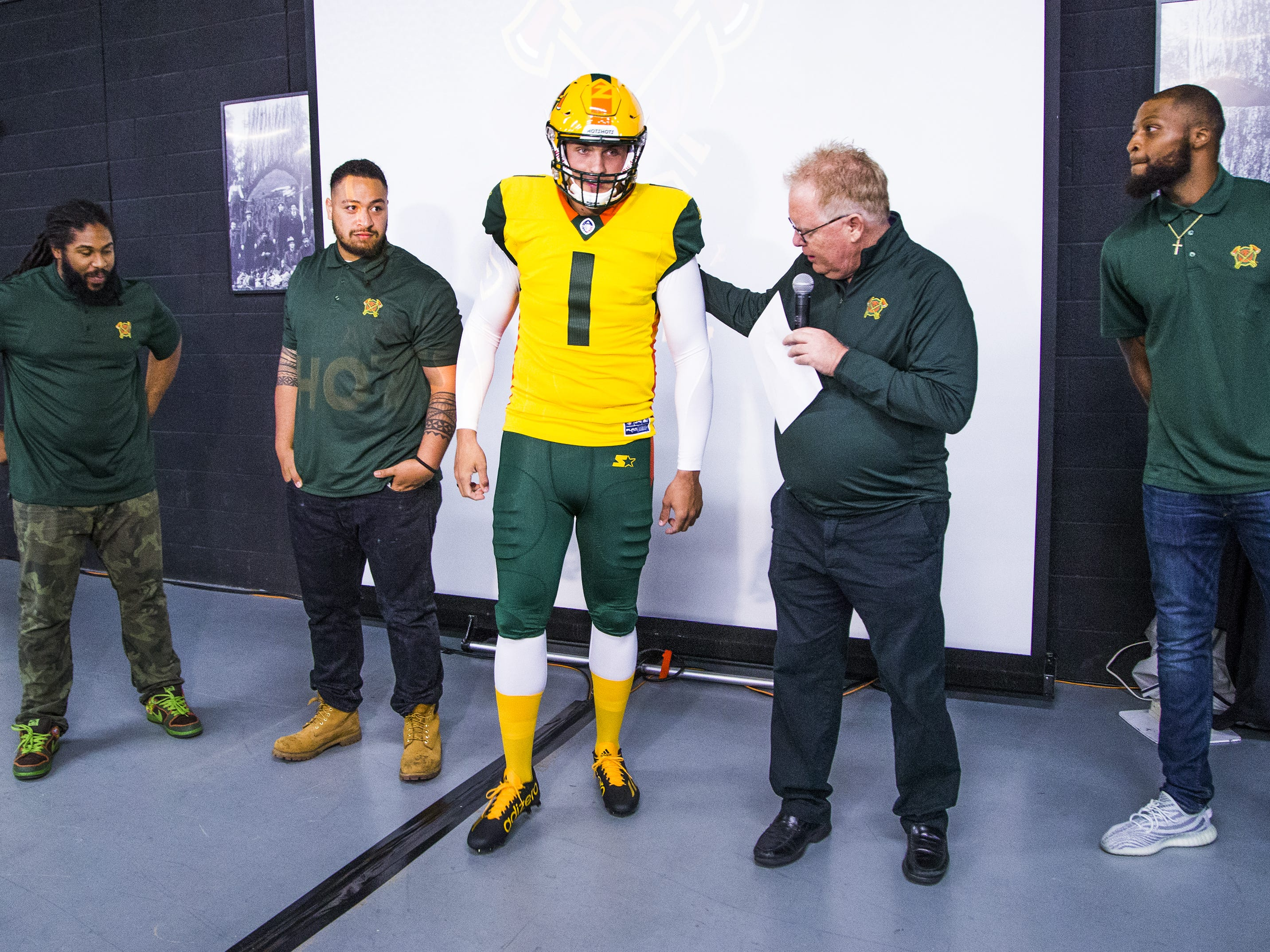 Nick Dooley, a longsnapper, wears the new uniform for the Arizona Hotshots professional football team as radio announcer Jeff Munn shows points out uniform details at an event at Lumberjaxes in Tempe, Tuesday, November 27, 2018.