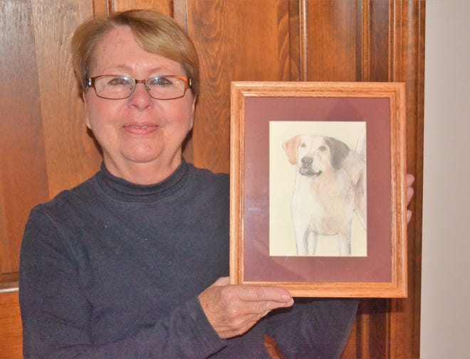 "Yvonne Leidorf holds a drawing of Tipper, who became famous in the Port Clinton area through her blog, ""Tipper's Tales."""