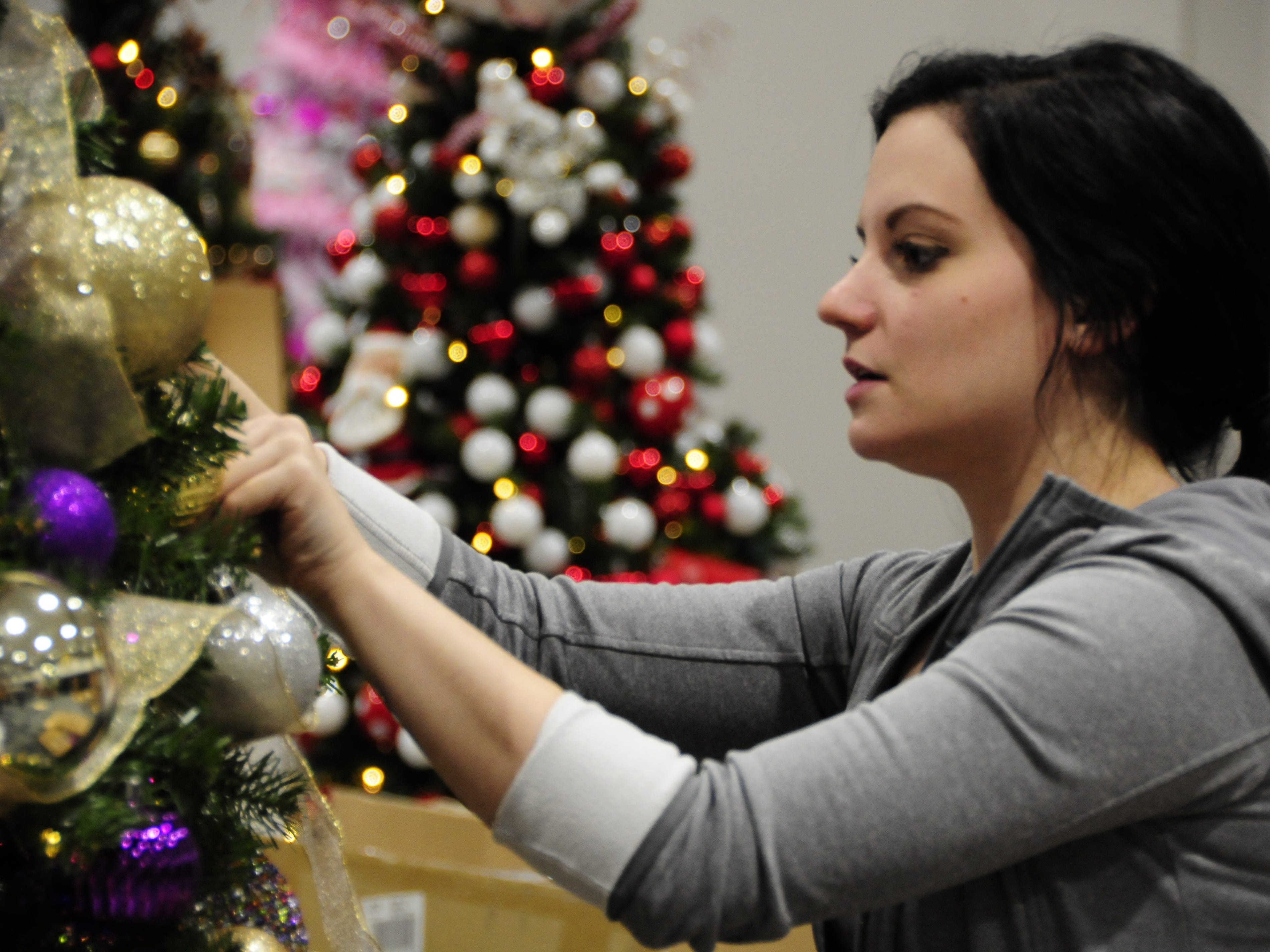 Destinee Yearkey decorates a tree Wednesday for the Festival of Trees, Friday through Sunday at the Blue Water Convention Center.