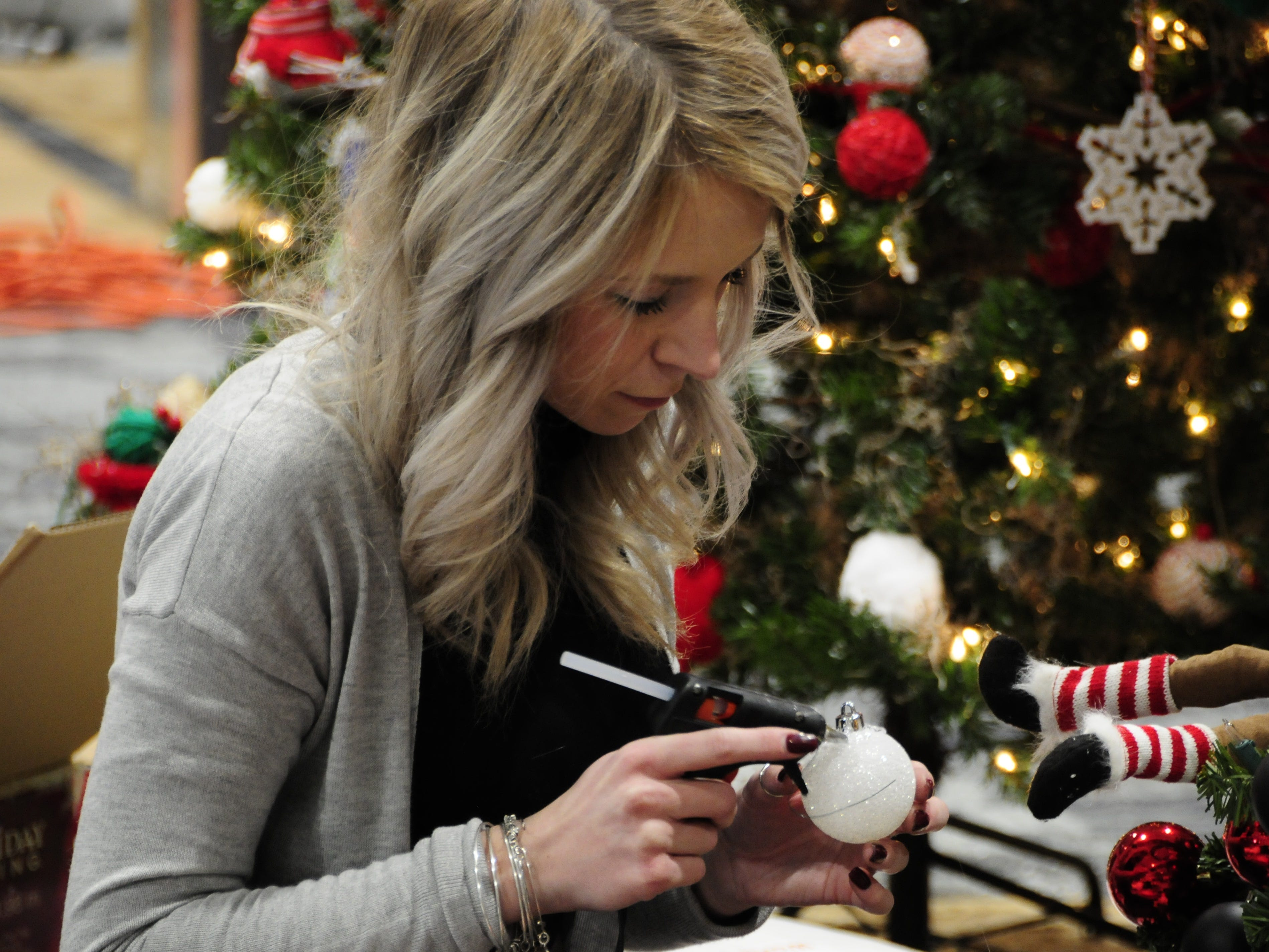 Brandi Bowman uses a hot glue gun to decorate a tree Wednesday for the Festival of Trees, Friday through Sunday at the Blue Water Convention Center.