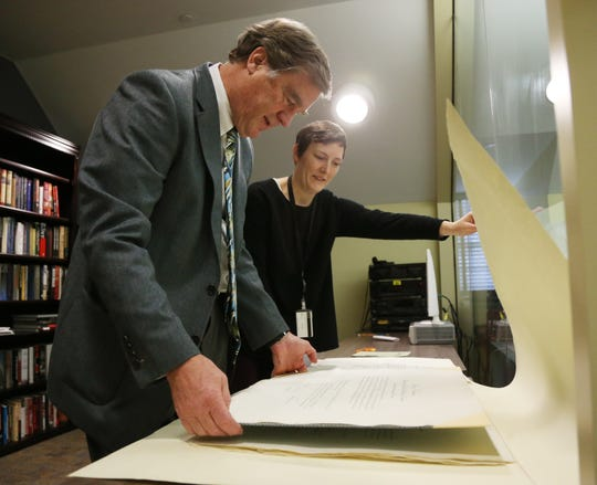 Paul Sparrow director of the FDR Library and Museum and supervisory archivist Kirsten Strigel Carter review the documents appointing Eleanor Roosevelt to the commission that authored the Universal Declaration of Human Rights in the museum's research room on November 28, 2018.