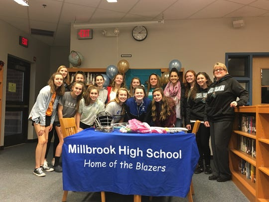 Claire Martell is surrounded by Millbrook lacrosse teammates and coaches on Tuesday after she signed a National Letter of Intent to play for Division I Coastal Carolina.