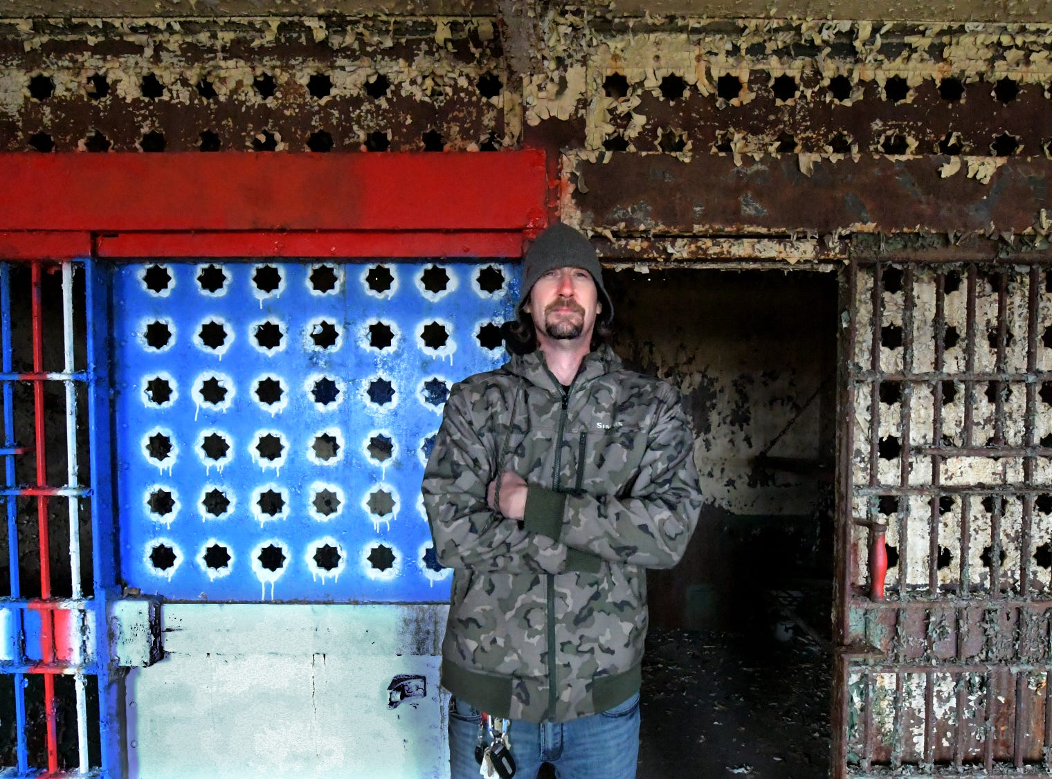 Think Loud building manager Scott Gracey poses for a portrait in front of a decorated cell while touring the former York County Prison on Chestnut Street in York City Wednesday, Nov. 28, 2018. United Fiber and Data has purchased the building and plans to incorporate the structure into a data center to accompany a 400-mile fiber-optic network it's building between New York and Virginia. Bill Kalina photo