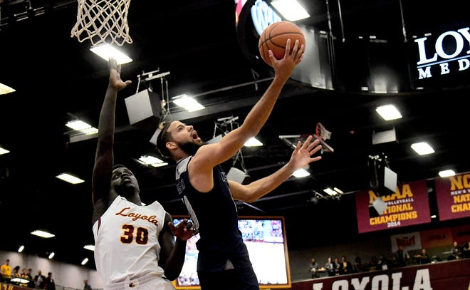 Nevada's Caleb Martin goes around Loyola's Aher Uguak during the first half of Tuesday night's game.