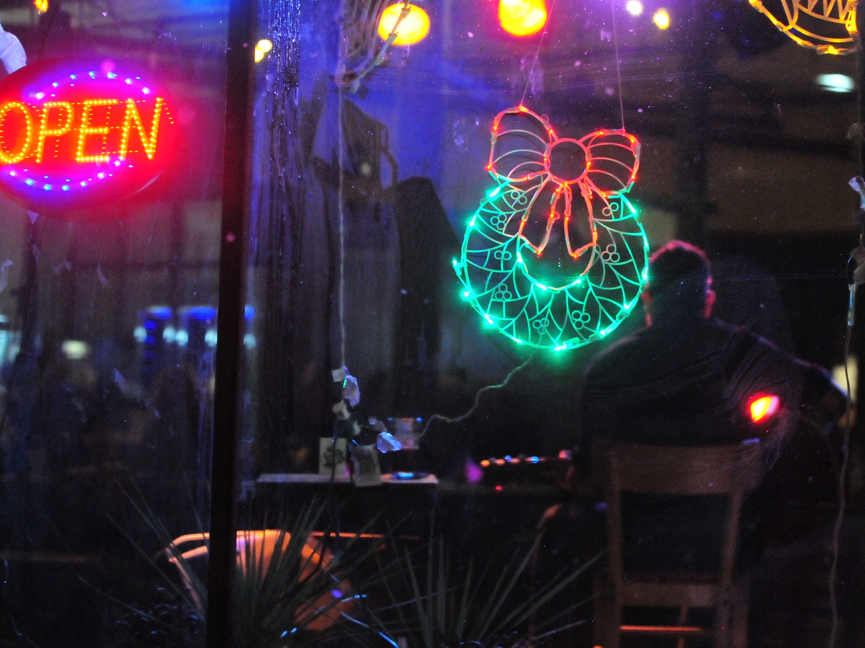 A musician entertains in a Depot District business Tuesday during the 14th annual Old-Fashioned Christmas Festival.