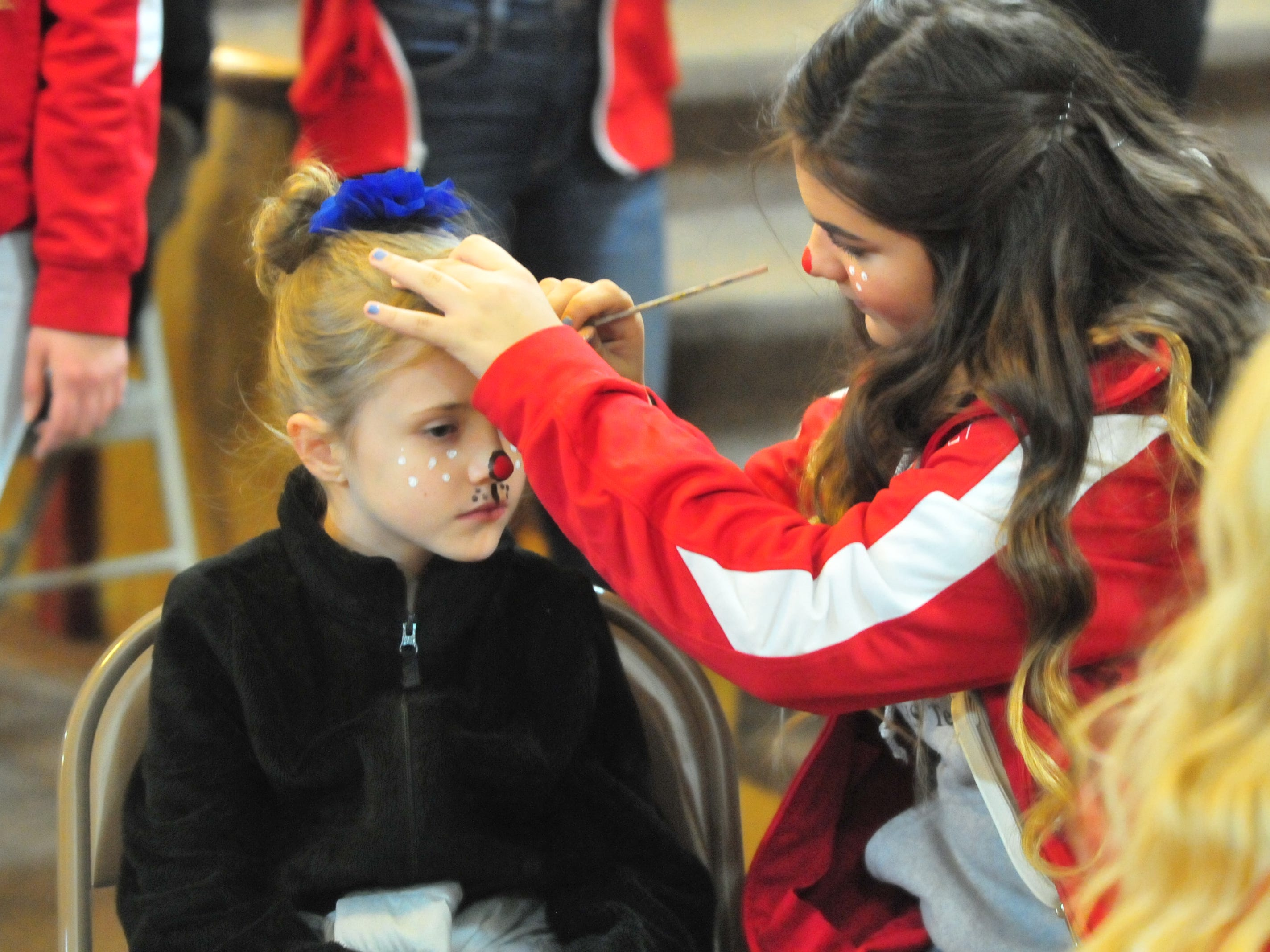 Richmond High School freshman Monica Segura, a cheerleader, paints Anna Beck, 8, to look like Rudolph the Red-Nosed Reindeer during Tuesday's 14th annual Old-Fashioned-Christmas Festival.