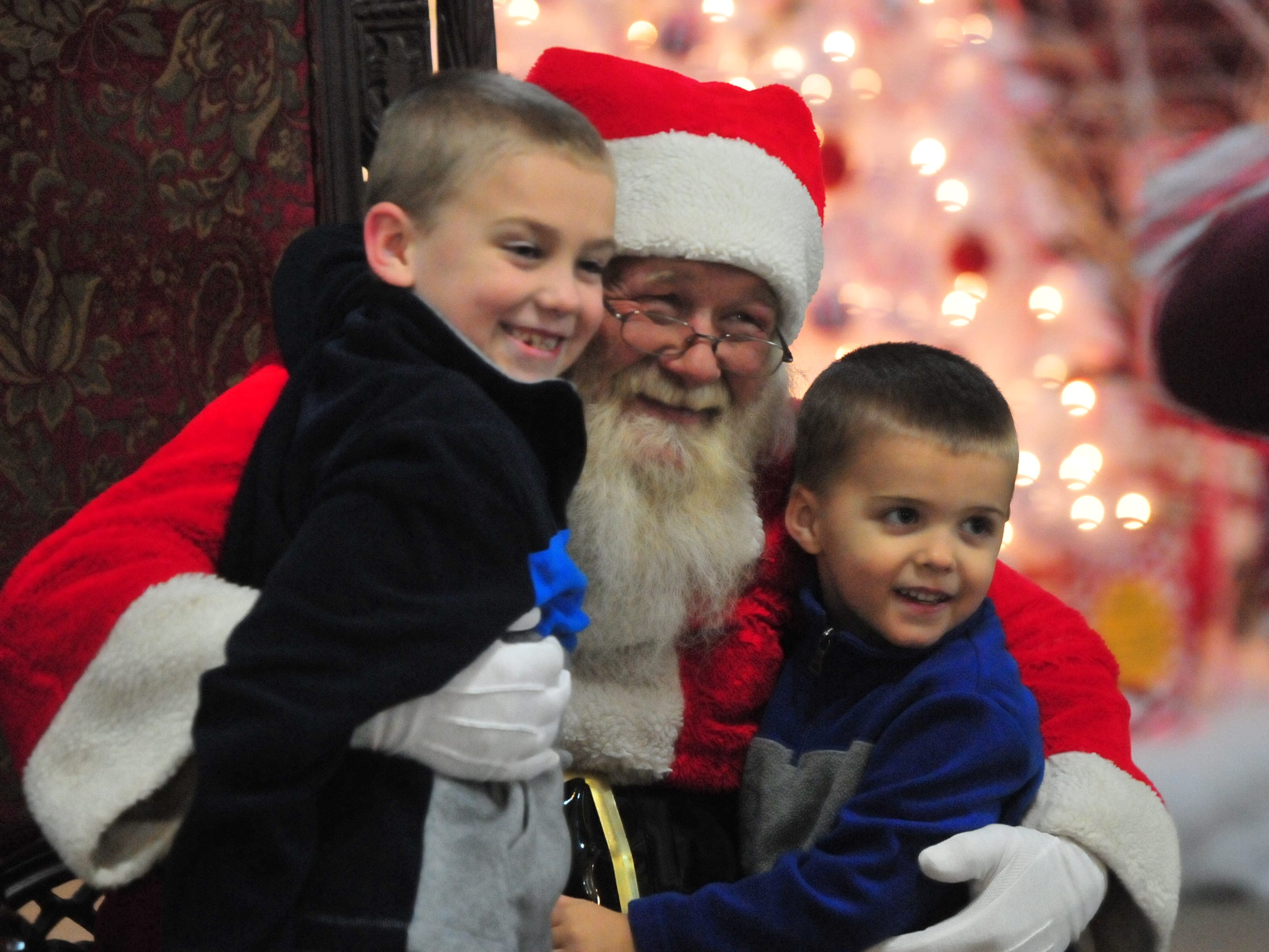 Brody Baugh, 7, and Bronson Baugh, 4, pose for a photograph with Santa during Tuesday's 14th annual Old-Fashioned Christmas Festival.