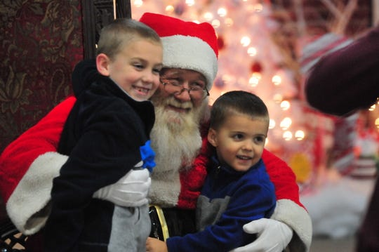 Two children post with Santa for photos during the 2018 Old Fashioned Christmas Festival.