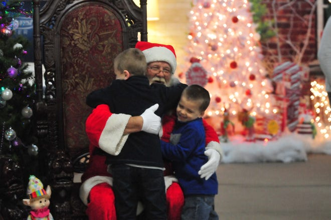 Brody Baugh, 7, and Bronson Baugh, 4, hug Santa on Tuesday during the Old-Fashioned Christmas Festival.