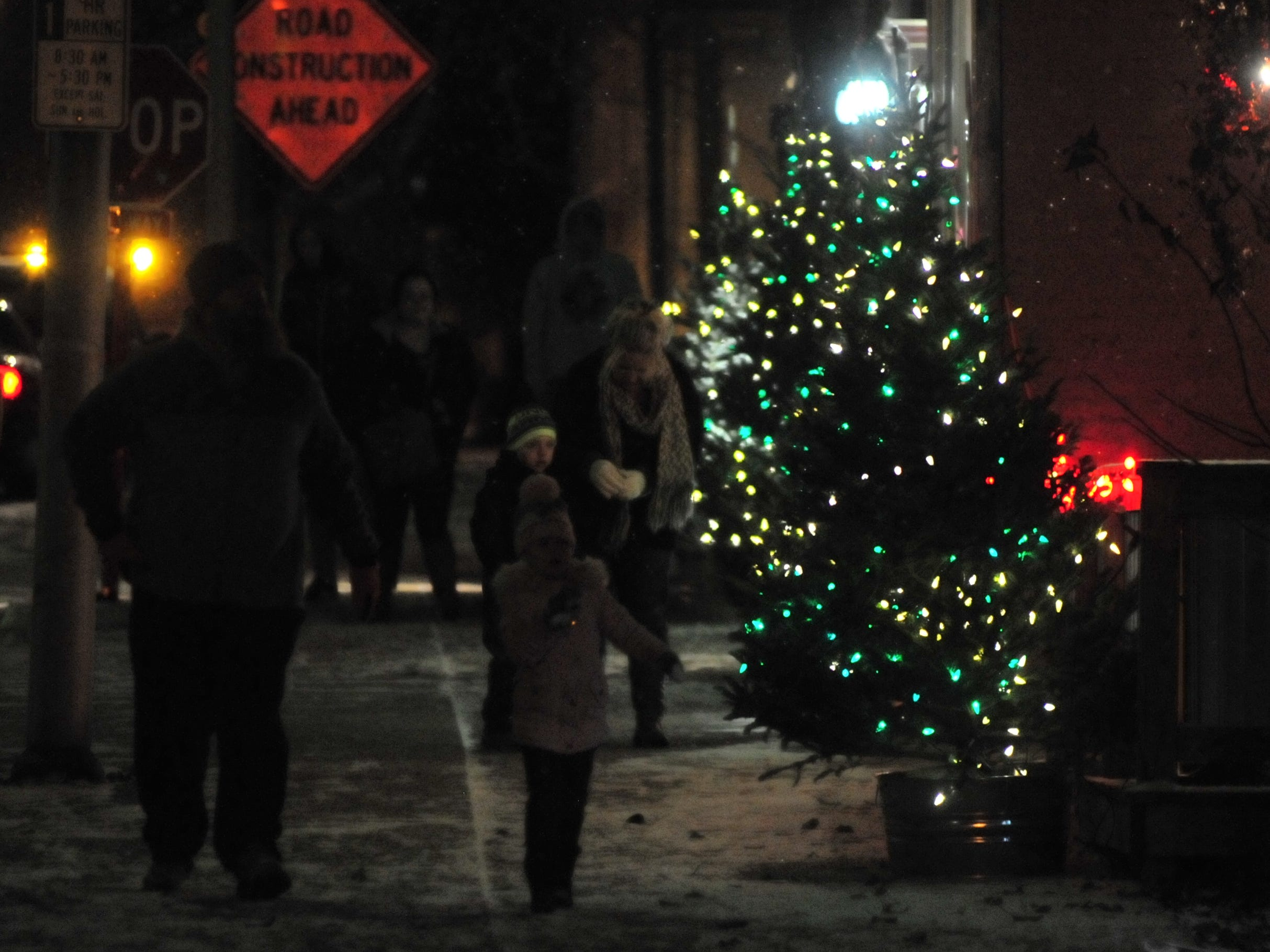 People walk down a sidewalk lined with decorations Tuesday during the 14th annual Old-Fashioned Christmas Festival.
