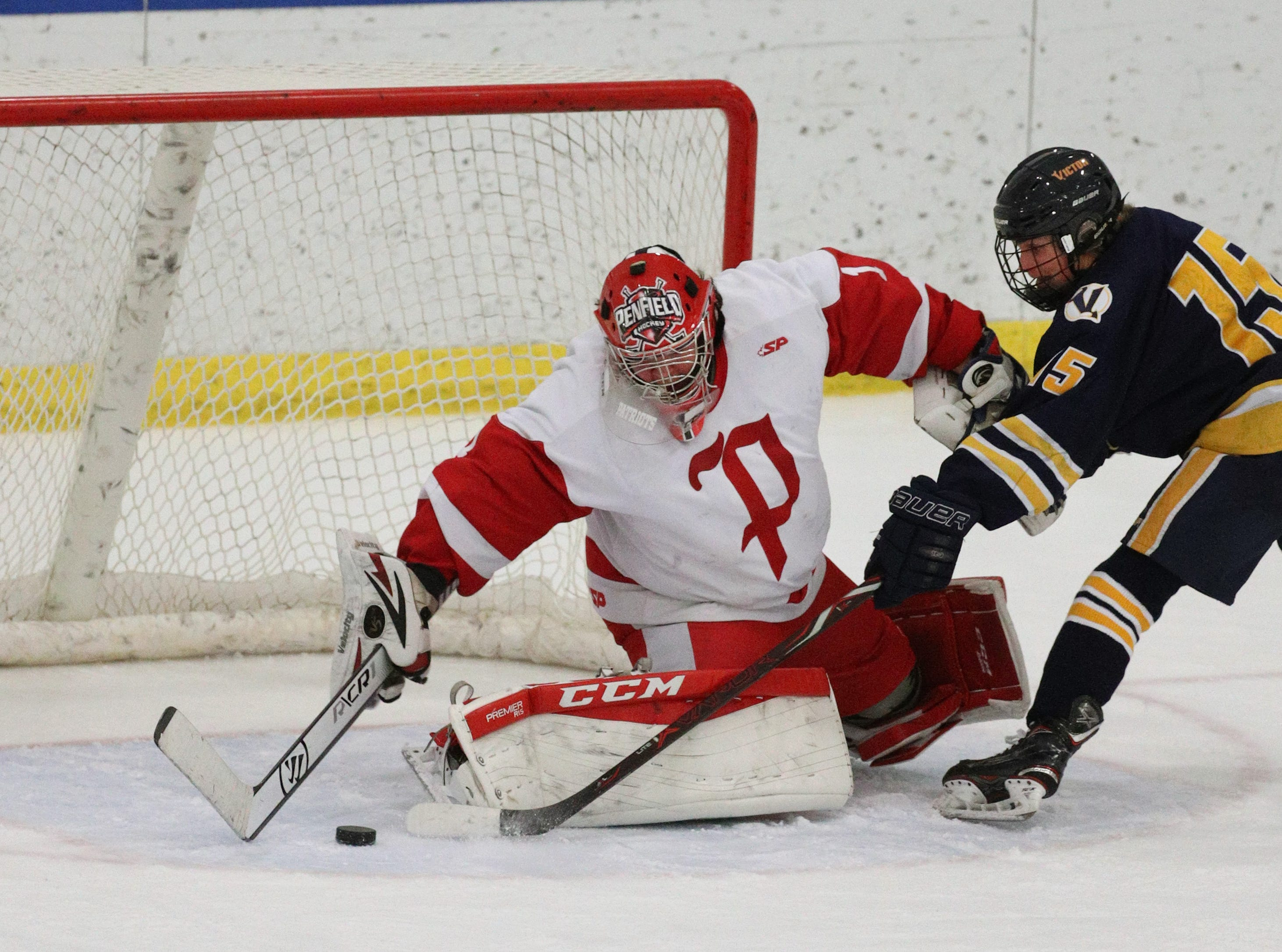 Penfield goalie Nick Andrade makes a stop against Victor's Lukas Miller.
