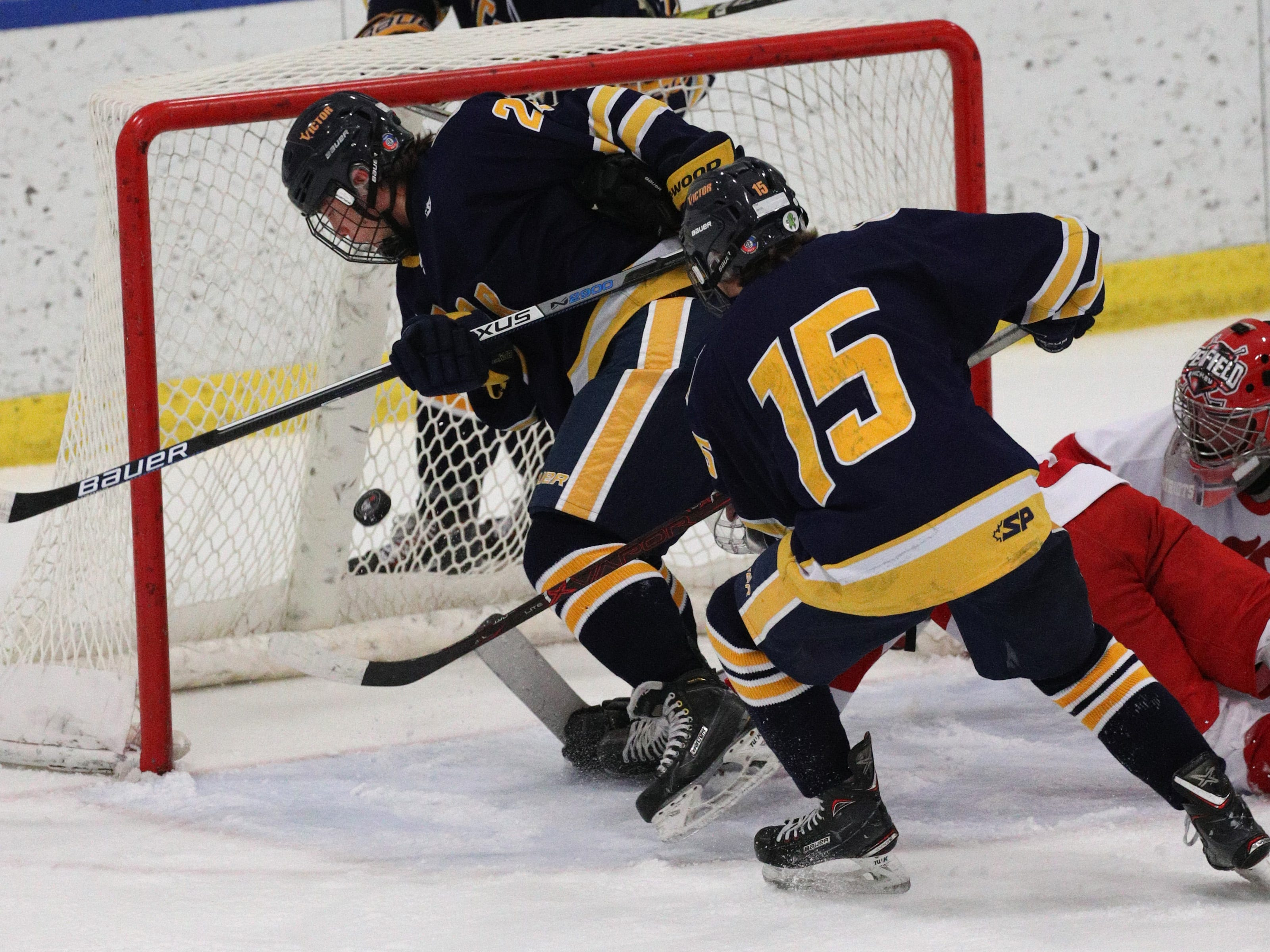 Victor's Lukas Miller (15) and Cal Lambert crash the net and score against Penfield.