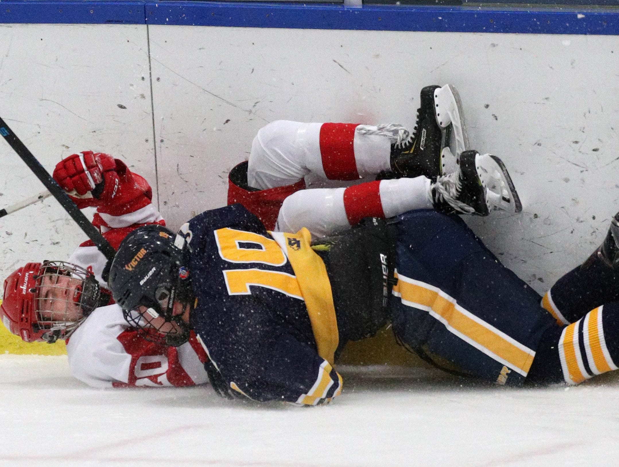 Penfield's Billy Kernan is checked by Victor's Alex Seiler (18).