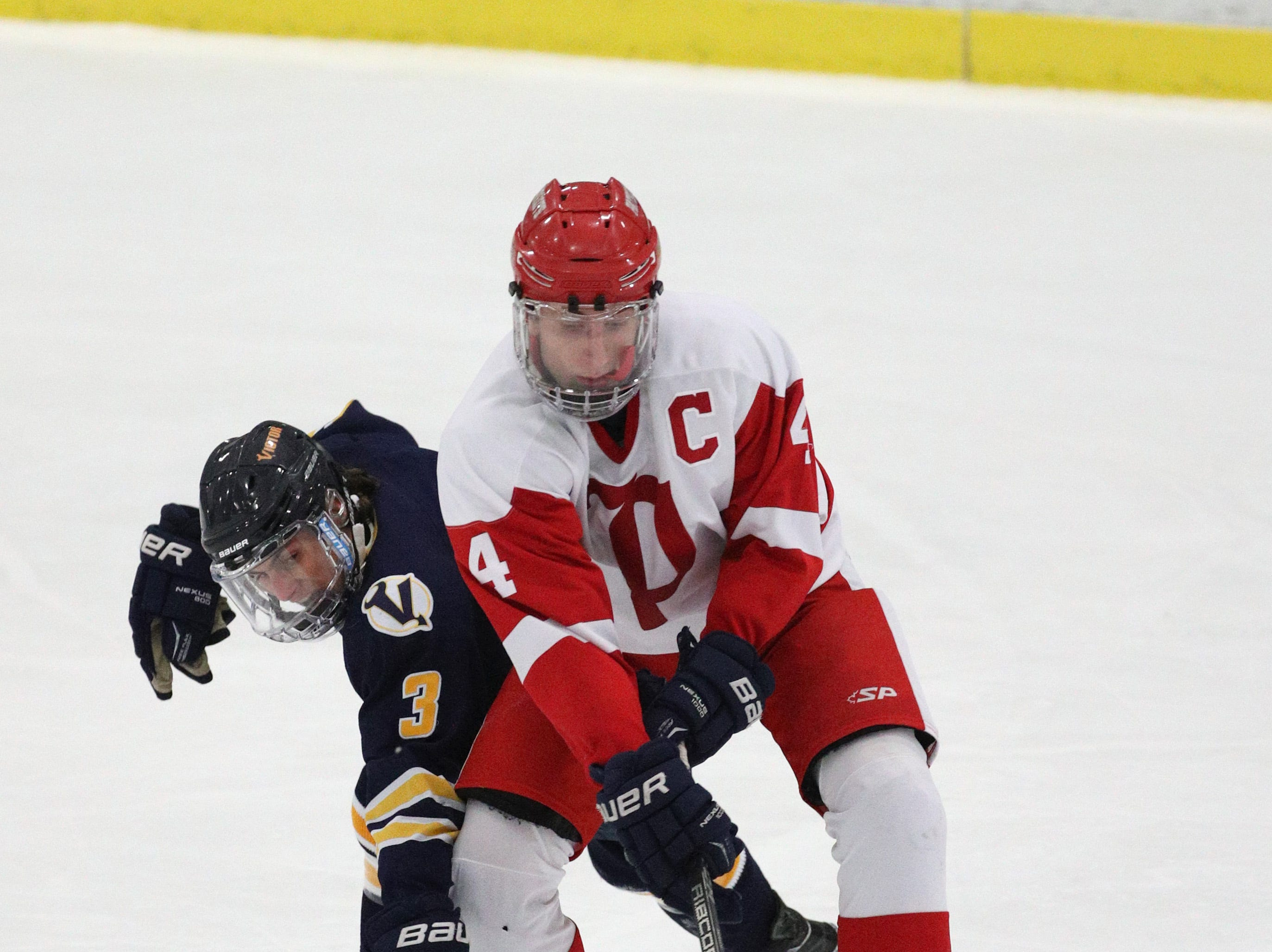 Victor's Josh Albert tips the puck away from Penfield's Jack Schlifke.