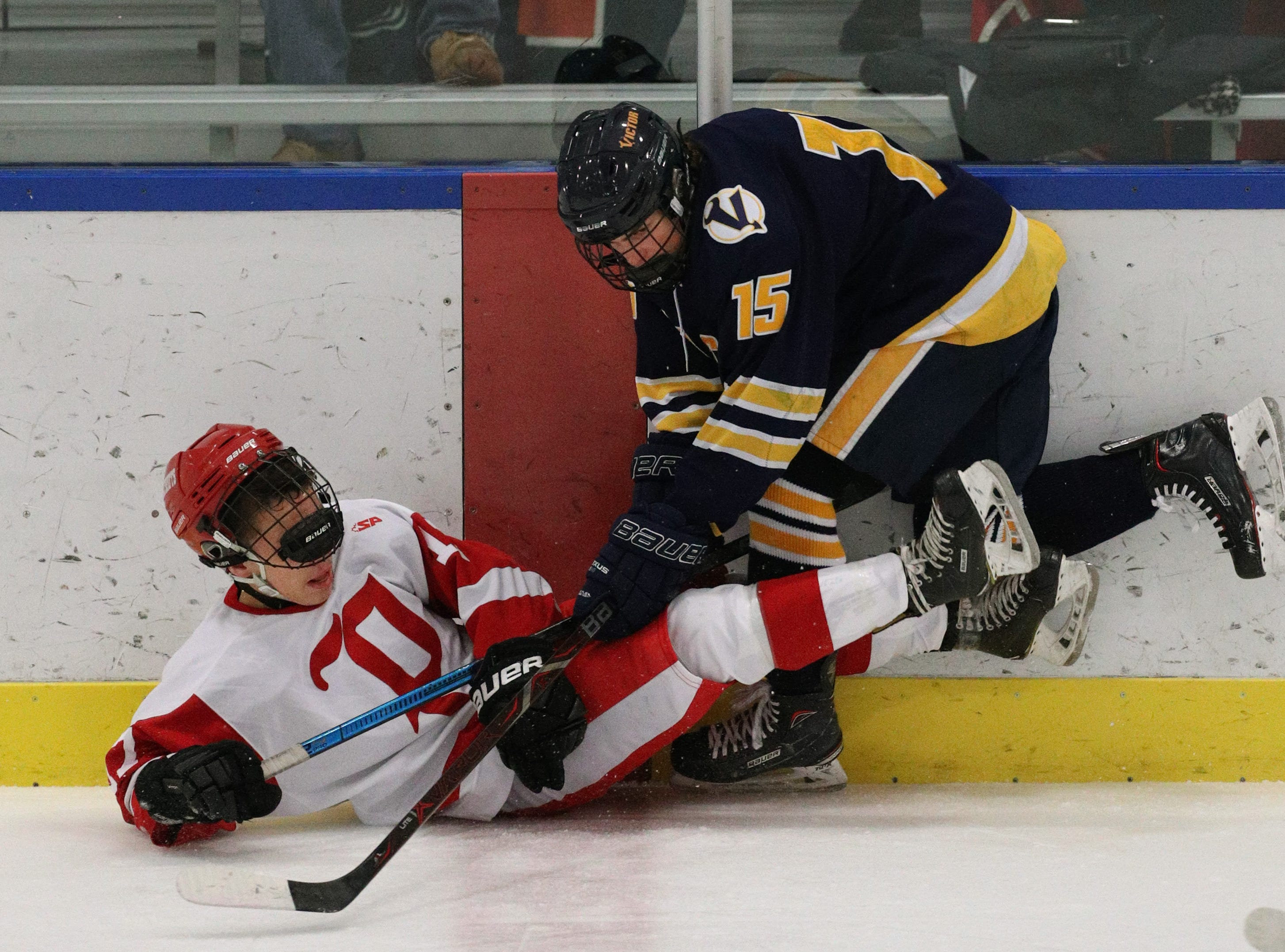 Penfield's Cody Stuewe  is checked to the ice by Victor's Lukas Miller (15).