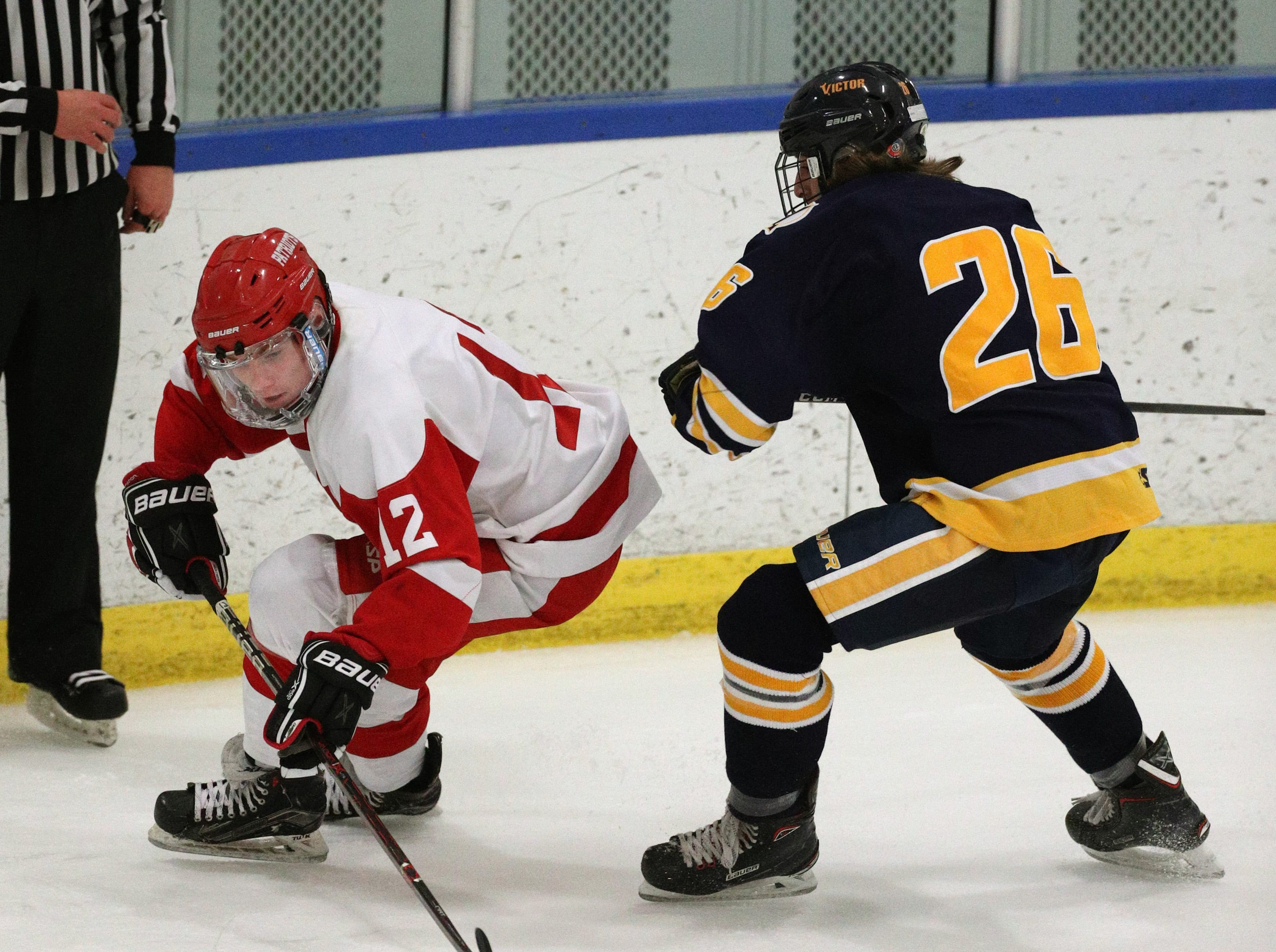 Penfield's Nathan Sobko (12) skates around Victor's James Tilley.