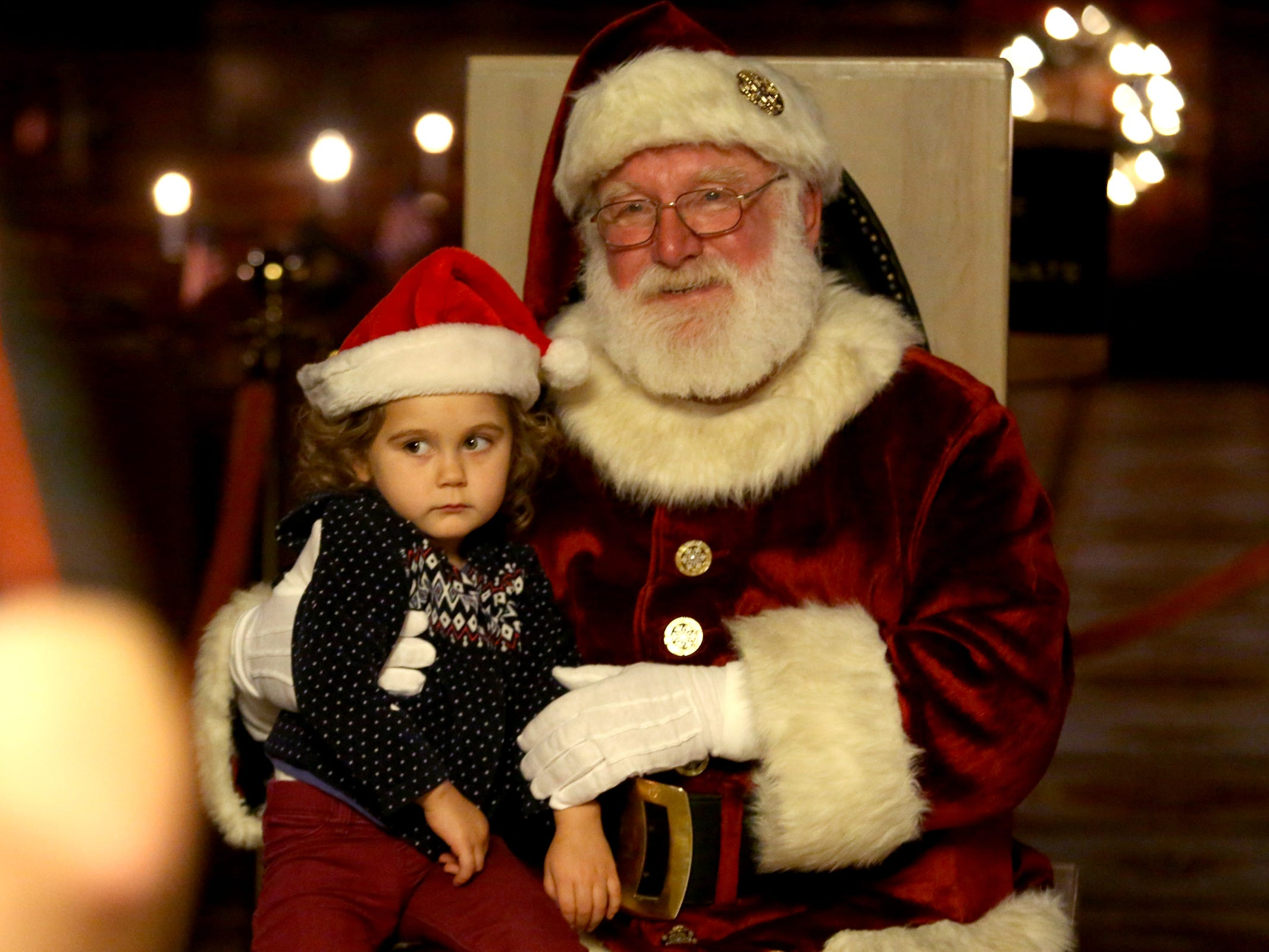 Tesla Lapsley, 2, of Salem, is held by Santa Claus during the Holiday Tree Lighting Celebration at the Oregon State Capitol in Salem on Tuesday, Nov. 27, 2018.
