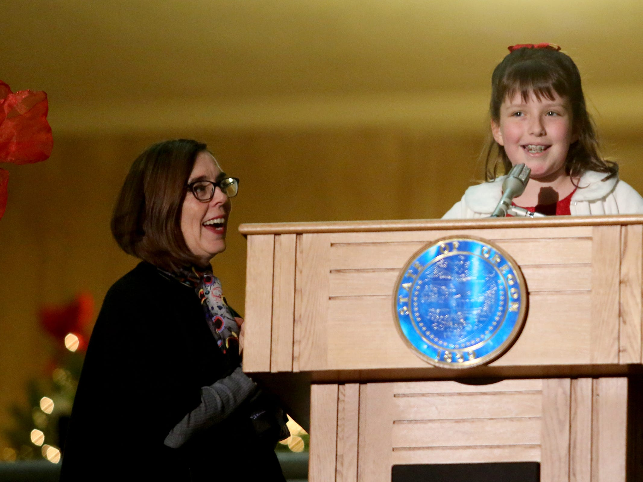 Brigette Harrington, the essay contest winner for the U.S. Capitol Christmas Tree Lighting Ceremony, speaks with Gov. Kate Brown during the Holiday Tree Lighting Celebration at the Oregon State Capitol in Salem on Tuesday, Nov. 27, 2018.