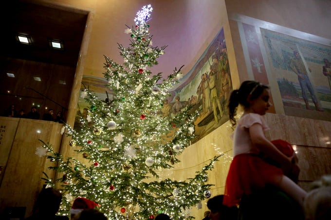 Beasley Manvel, 4, sits on the shoulders of her dad, Evan Manvel, of Salem, during the Holiday Tree Lighting Celebration at the Oregon State Capitol in Salem on Tuesday, Nov. 27, 2018.
