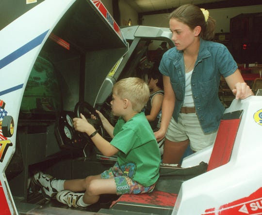 Cory David enjoys a video game in the Shakey's Pizza Game Room as Leigh Anne Lunsford looks on in this 1998 file photo.