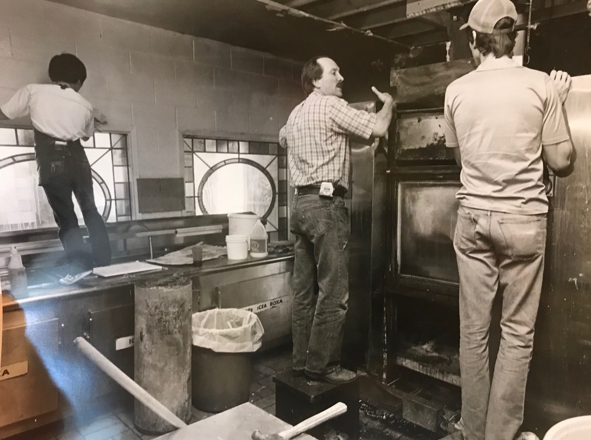 Shakey's Pizza owner John Dean, center, surveys the damage to an oven after a fire damaged the restaurant in March of 1983.