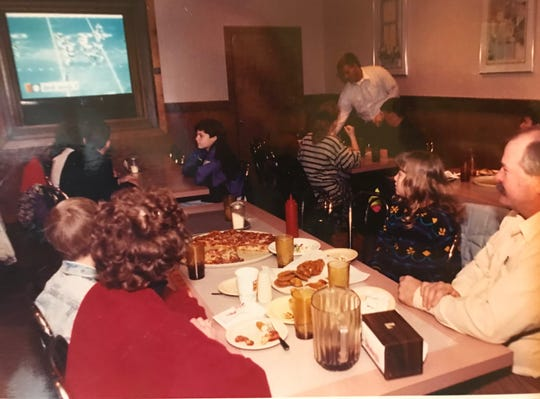 The Heathcott family of Veribest enjoys a football game while eating at Shakey's Pizza in San Angelo in this January 1992 file photo.