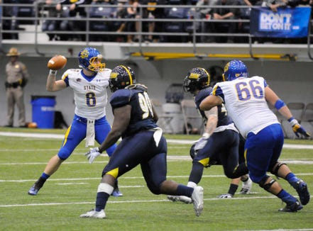 South Dakota State quarterback Austin Sumner (6) looks for an opening as Northern Arizona defenders close in during an NCAA college football game Saturday, Nov. 30, 2013, in Flagstaff, Ariz. South Dakota State won 26-7.