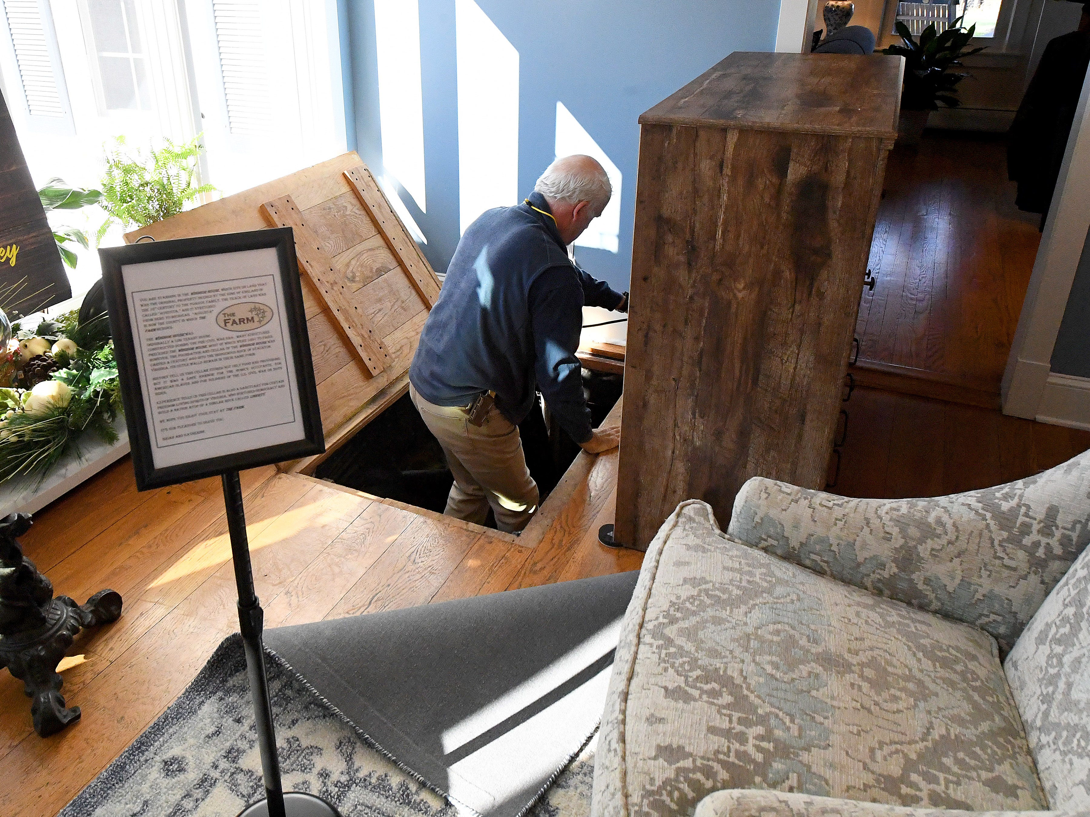 Co-owner and innkeeper Brian Westenberg descends into the normally hidden entrance of the basement at the Inn at WestShire Farms in Staunton on Wednesday, Nov. 28, 2018.
