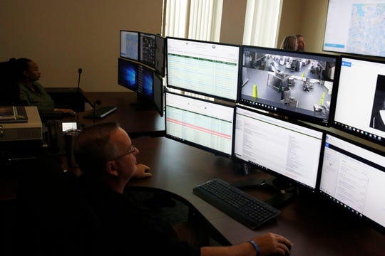Leon County Sheriff's Office Capt. and analyst Jimmy Goodman, foreground, and analyst Chelsea Grant monitor the newly developed Real Time Crime Center.
