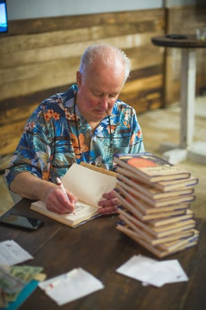Pat Williams, author, motivational speaker and senior vice president of the Orlando Magic, signs his book at a Meet & Greet Event at Twisted Oak Farms.