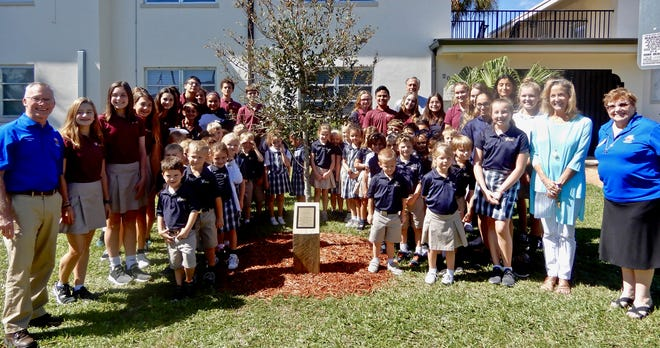 St. Helen Catholic School kindergarten and eighth-grade students together with Deacon Dave Hankle, Principal Lisa Bell, Vero Beach City Councilman Tony Young and Vice-Chair Vero Beach Tree & Beautification Commission Marilyn Dussault at a recent Centennial Tree dedication ceremony.