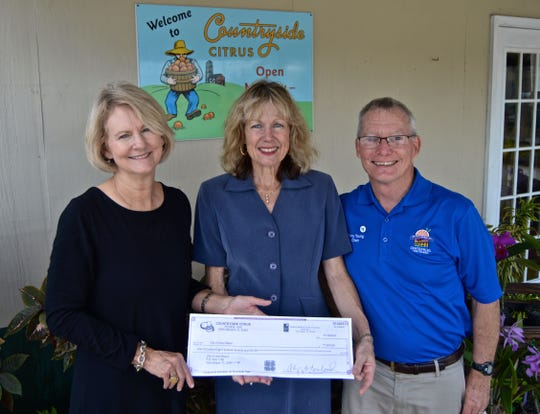 Cheryl Roseland, left, of Countryside Citrus, presents a check for $1,870 to Vero Beach City Clerk Tammy Bursick and City Councilman Tony Young for the Centennial MacWilliam Park Restoration Project.
