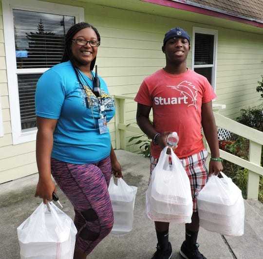 Local residents Bria Anderson, left, and Cordell Jones get their meals to go at the Gertrude Walden Child Care Center Community Dinner.