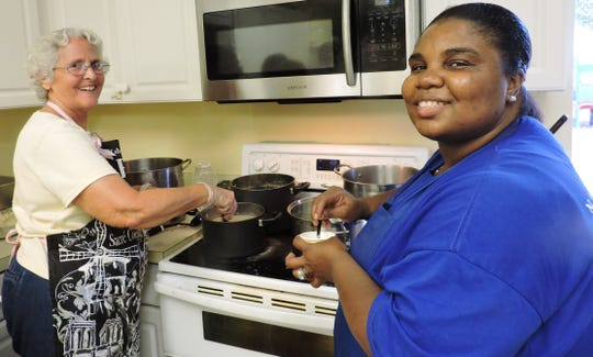 Sharon Fagley, left, and Tamika Williams stir up delicious food at the Gertrude Walden Child Care Center Community Dinner.